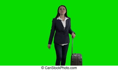 Woman with luggage waving her hand saying hello against...