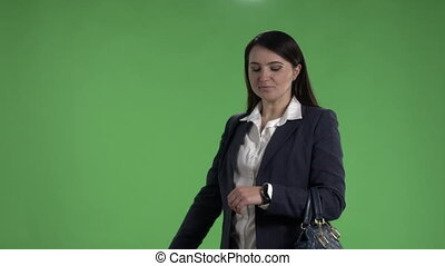 Business woman looking at watch and waving to taxi against a green screen