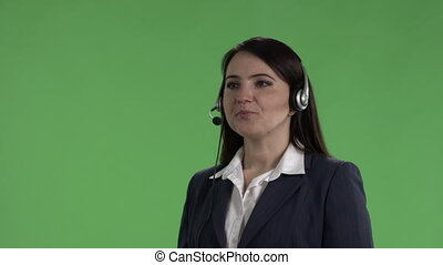 Customer service representative with headset takes phone call against green screen