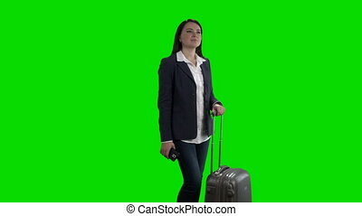 Woman traveling with rolling suitcase standing against green screen
