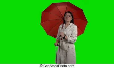 Woman with red umbrella and suitcase waving to taxi against...