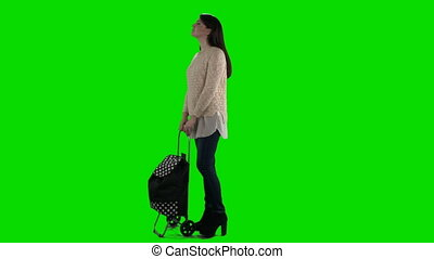 Woman with shopping bag on wheels against green screen