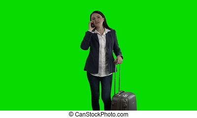 Woman with suitcase talking on the phone waving her hand...