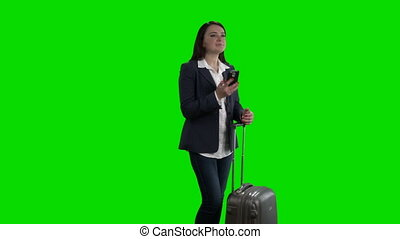 Woman with rolling suitcase talking on the phone against green screen