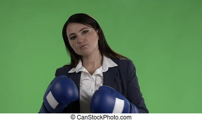 Slow motion of serious business woman with boxing gloves ready to fight against green screen
