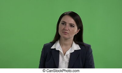 Woman in business suit having conversation with someone against green screen
