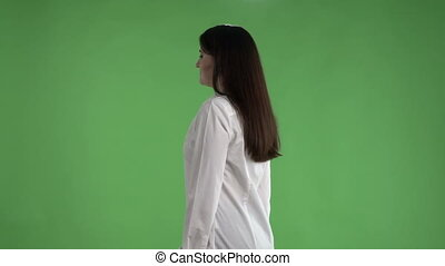Brunette business woman in white shirt talking to camera against a green screen