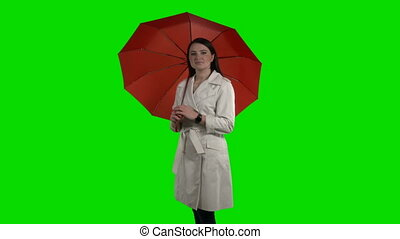 Brunette woman under red umbrella looking at watch against...