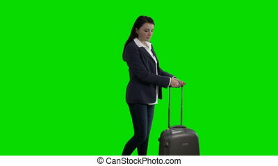 Woman traveling with suitcase looking up checking schedule...
