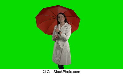 Happy woman under red umbrella looking at camera waving her hand against green screen