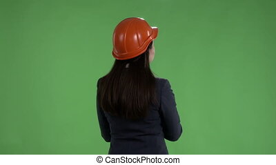 Rear view of female engineer in safety helmet against a green screen
