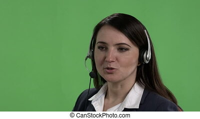 Face of female call centre worker with headset against green...