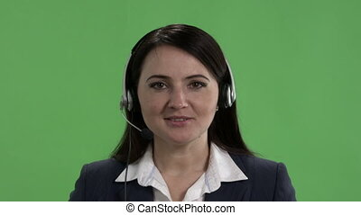 Female call centre worker with headset takes phone call talking to camera