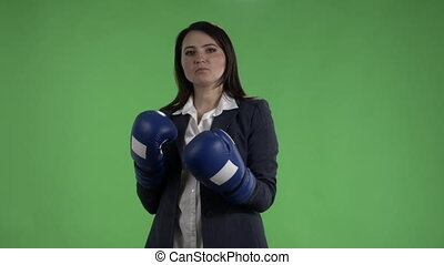 Serious business woman with boxing gloves punching against...