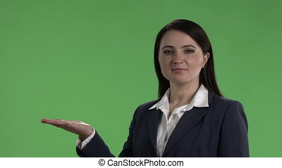 Business woman with presentation gesture talking to camera against green screen