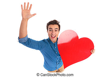 amazed young man holding a red heart