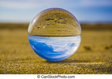 Glass ball lying in the sand against the background of the...