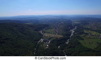 Aerial flight over Polovragi commune and green hills,...