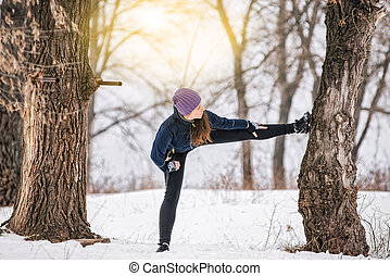 girl athlete in the winter in the park doing stretching...