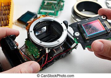 Old scratched image sensor digital SLR camera in hands of...