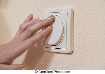 Womans hand with finger on light switch to turn off the...