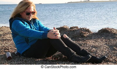 Blonde sad woman sitting at the seaside - Thoughtful,...