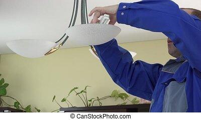 man change light bulb in chandelier. - man change light bulb...