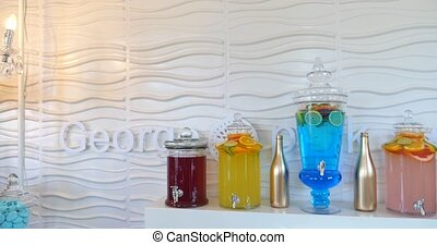 Bottles of multi-color drinks with ice on white background.