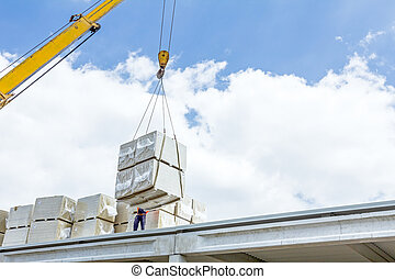 Mobile crane is raising package of glass wool on the roof huge unfinished hall