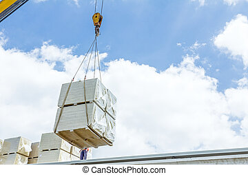 Mobile crane is raising package of glass wool on the roof...