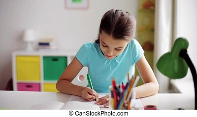 happy girl with book writing to notebook at home - people,...