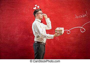 Young funny man with gift on red studio background. The...