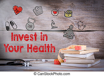Invest in your health. Stack of books and a stethoscope on a wooden background
