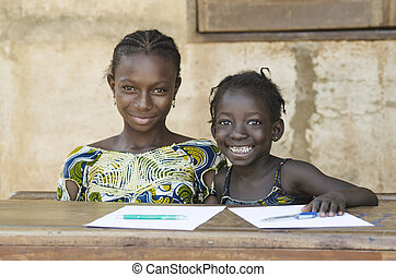Two African Ethnicity Children Smiling Studying in a School...