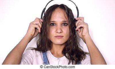 Young beautiful curly woman wears headphones listening music joyful dancing against a white background in slow motion.