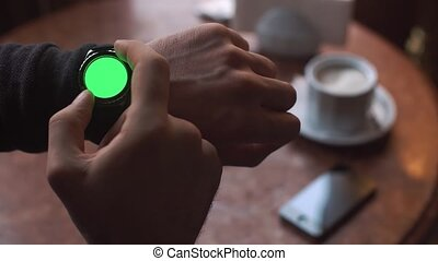 Man hands gestures on a round screen modern smartwatch with...