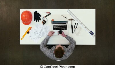 Office engineer using mobile phone sitting at his desk. Top...