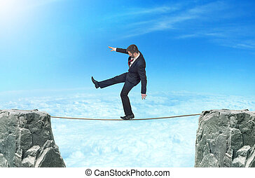 Concept of Goal. A man in a business suit walking on the rope over the precipice on sky background. Overcoming obstacles. Aspiration to success.