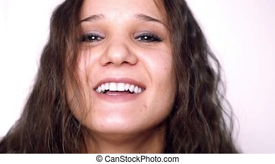 Closeup portrait of beautiful young woman with curly hair smiling isolated on white background in slowmotion.