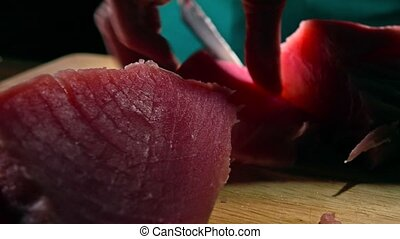 Woman cutting tuna fillet. close-up dolly shot - Woman...