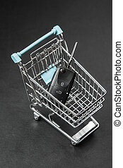 Car keys in a shopping cart on dark background