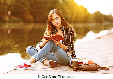 Young beautiful girl sitting on pier