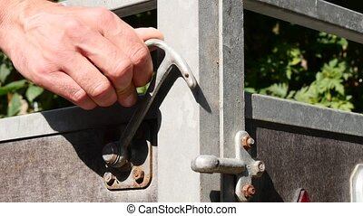 Male hand close and open trailer lock - Male hand closes and...