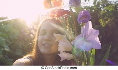Young thoughtful beautiful woman in flowers outdoor at sunset through the sun in slow motion with lense flare effects. 1920x1080