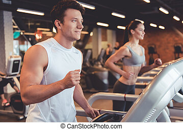 At the gym - Attractive young muscular man is smiling while...