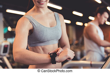 At the gym - Attractive young woman is looking at her...