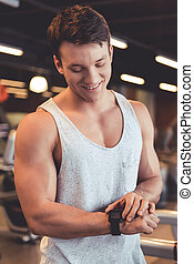 Man at the gym - Attractive young muscular man is looking at...