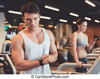 At the gym - Attractive young muscular man is looking at his...