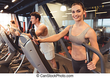 At the gym - Attractive young people are smiling while...