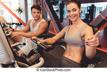 At the gym - Attractive young people are talking and smiling...